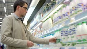 An adult man chooses products in the store he considers a bottle of milk. An adult man holds a plastic bottle of milk in his hand, people look at food in a super stock video footage