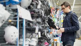 An adult man chooses roller skates for his daughter, he is in the mall stock video