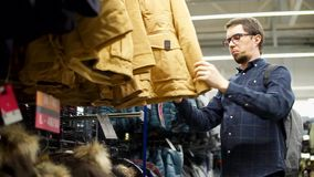 An adult man chooses a winter jacket, clothes are on a rack in a shopping center stock video footage