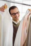 Adult man choosing shirt in clothes shop Royalty Free Stock Images