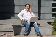 Adult man with computer and mobile phone Stock Photos