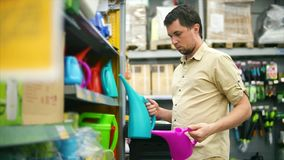 An adult man considers a variety of watering cans to water the flowers stock footage