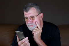 Adult Man Contemplates His Mobile Phone. An adult man watches his mobile phone Royalty Free Stock Image