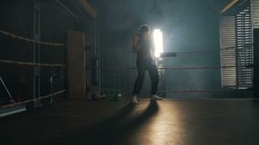 Adult man crouch and boxing on the ring with yellow ropes in industrial interior. Kickboxer training in light rays slow motion stock footage