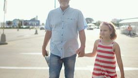 An adult man and a curly girl go from the parking lot to the supermarket. Father and daughter, father`s day. Family. Leisure, shopping stock video footage