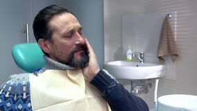 Adult man in dental chair. stock video footage