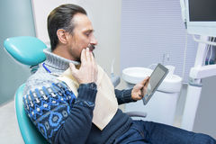 Adult man in dental office. Guy with toothache holding tablet. Precise diagnosis and effective treatment royalty free stock image