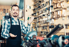 Adult man displaying his tools for making keys. Adult man worker displaying his tools for making keys in workshop Royalty Free Stock Photography