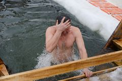 Adult man dive. Yoshkar-Ola, Russia - January 19, 2017 Adult man dive into an ice hole in the feast Epiphany stock photo