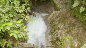 Adult man doing canyoning jumping into a high waterfall dolly shot. Adult man doing canyoning jumping into a high waterfall in Ecuador dolly shot stock video footage