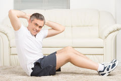 Adult man doing sit ups on floor. Stock Photography