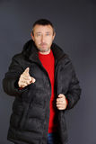 Adult man dressed in black jacket points his finger Royalty Free Stock Photo