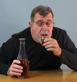 Adult Man Drinking Alcohol. An adult man lifts a shot glass full of whiskey to his lips for his next shot of alcohol Stock Photography