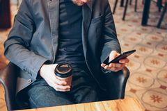 Adult man drinking coffee from paper cup and using mobile phone at cafe. Shop young casual person browsing lifestyle beard use handsome modern internet stock image