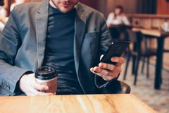 Adult man drinking coffee from paper cup and using mobile phone at cafe. The Adult man drinking coffee from paper cup and using mobile phone at cafe shop young royalty free stock image