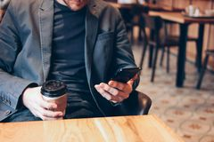Adult man drinking coffee from paper cup and using mobile phone at cafe. The Adult man drinking coffee from paper cup and using mobile phone at cafe shop young stock photography