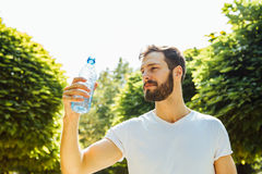 Adult man drinking water from a bottle outside stock images
