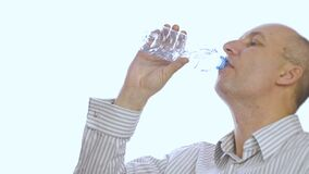 Adult man drinking water from plastic bottle on white background. Thirsty man drinking water from bottle isolated close up stock footage