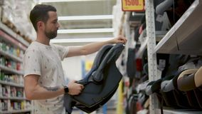 Adult man is examining a child car seat in shop, rotating and looking it around stock video footage