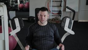 Adult man with excess weight trains his chest on the simulator. Adult man with excess weight trains his chest on the simulator stock video footage