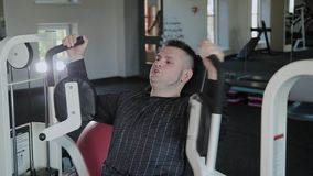 Adult man with excess weight trains his chest on the simulator. Adult man with excess weight trains his chest on the simulator stock video