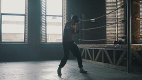 Adult man fights the shadow training near boxing ring in industrial gym. With windows. Light weight kickboxer training stock video footage