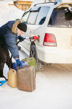 Adult man fills a car with petrol at a fuel station Royalty Free Stock Images