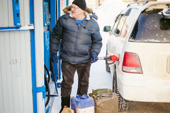 Adult man fills a car with petrol at a fuel station Stock Photos