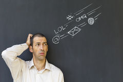 Adult man frustrated and stressed from social media overload. Single white adult man standing in front of a blackboard with drawn social media icons symbolizing Stock Image