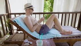 An adult man in glasses enjoys the music he listens on his mobile phone during the day, the person is lying on a. A smiling man who wore sunglasses and a hat on stock video footage