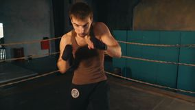 Adult man without gloves fights the shadow on boxing ring in industrial gym. Slow motion POV boxer training stock footage