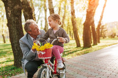 Adult man with granddaughter on bike. Senior men talking to little granddaughter sitting on bicycle in park. Horizontal outdoors shot stock photo