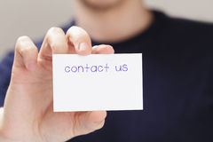 Adult man hand  holding card contact us. In front of camera, blurred background Stock Images