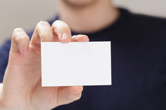 Adult man hand holding empty business card in front of camera royalty free stock photos