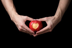 Adult man hands holding apple with carved heart Royalty Free Stock Photos