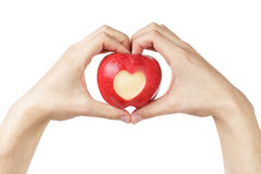 Adult man hands holding apple with carved heart Royalty Free Stock Photography