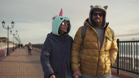 An adult man and his girlfriend are walking along the street on a sunny day. An adult man in sunglasses and his wife who is dressed in a unicorn suit are walking stock video footage
