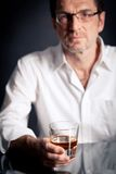 Adult man holding an alcoholic drink Royalty Free Stock Image