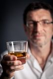 Adult man holding an alcoholic drink Royalty Free Stock Photos