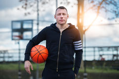 Adult man holding basketball ball standing on street basketball playground at sunset time Stock Images