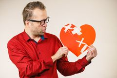 Adult man holding broken heart Stock Images