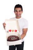 Adult man holding a chocolate birthday cake. A smiling man holds a chocolate birthday cake decorated with love hearts in a cake box Royalty Free Stock Photo