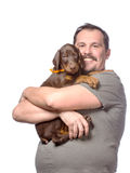 Adult man is holding his sweet puppy isolated on white backgroun Royalty Free Stock Image