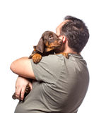 Adult man is holding his sweet puppy isolated on white backgroun Stock Images