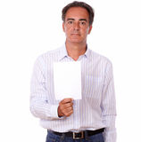Adult man holding a white card with copyspace. Portrait of an adult man on stylish shirt holding up a blank white card while standing on isolated background Royalty Free Stock Photography