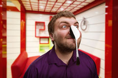 Adult man holds a spoon on his nose Royalty Free Stock Images