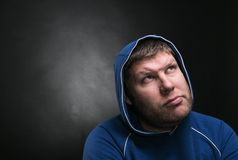 Adult man in the hood sits thinking. On dark background Royalty Free Stock Photos