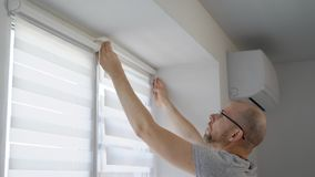 Adult man is installing a rod for blinds on a window frame in a living room in daytime and fixing curtains. Checking serviceability stock video footage