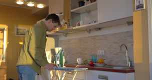 Adult Man Ironing White Shirt In The Kitchen stock video