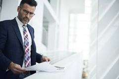 Adult man in a jacket and glasses  creating optimal processes to improve work and increase income Royalty Free Stock Images